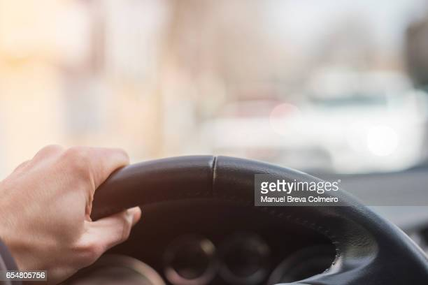 a man's hand grips the steering wheel of his car firmly - hybrid car stock photos and pictures