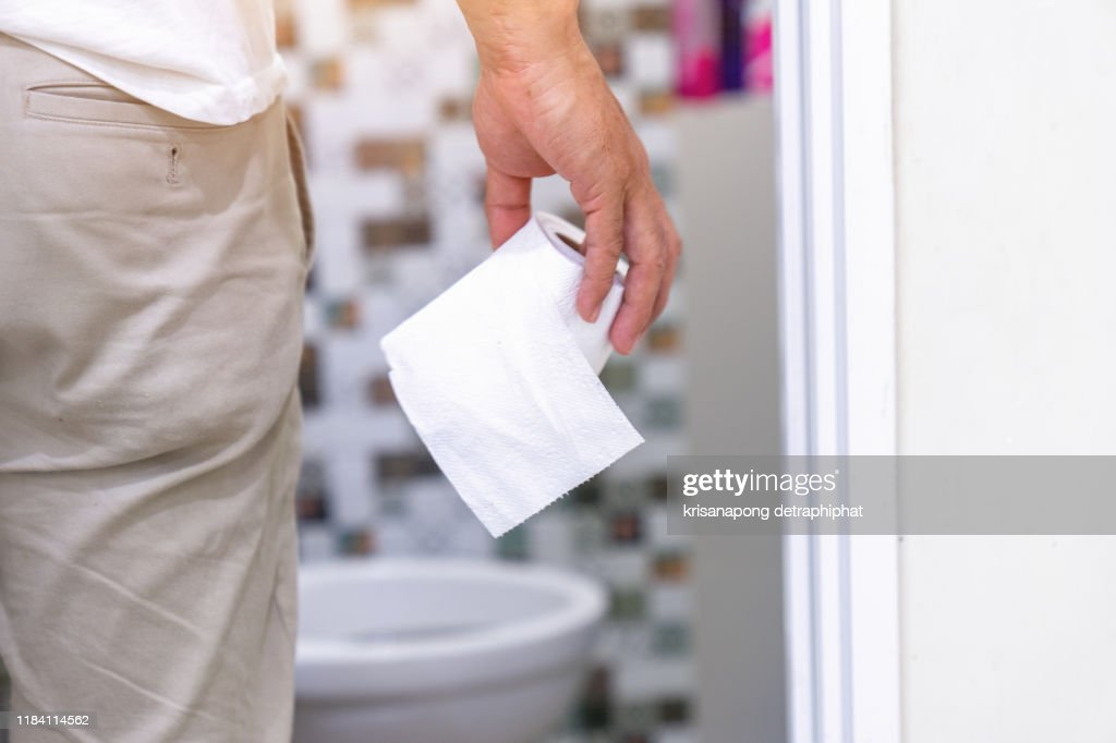 Man's hand, he holds a roll of toilet paper Going to the bathroom Toilet toilet background : Stock Photo