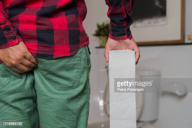man's hand, he holds a roll of toilet paper going to the bathroom toilet toilet background - apendicitis fotografías e imágenes de stock