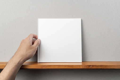 man's hand hold white square notebook on bookshelf 1136939097