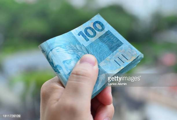 man's hand holding a bundle of brazilian 100 reais banknotes - carlos alkmin stock pictures, royalty-free photos & images