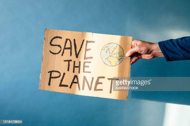 man's hand holding a cardboard sign that says save the planet - demonstration stock pictures, royalty-free photos & images