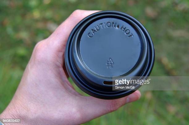 Man's hand holding a disposable coffee cup with a black plastic lid