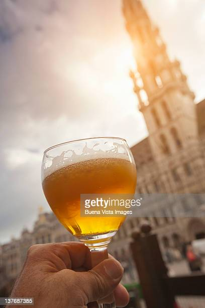 Man's hand holding a glass of beer
