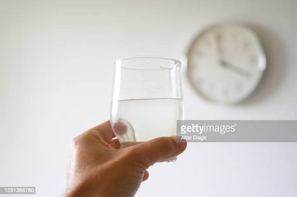 man's hand holding a glass of water, in the background is a wall clock. - honour stock pictures, royalty-free photos & images