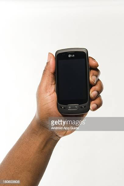 A man's hand holding a LG Optimus One smartphone during a studio shoot for Android App Guide February 11 2011