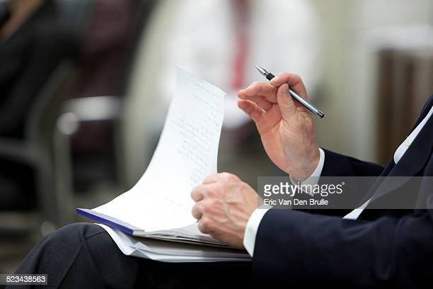 man's hand holding a pen holding a note pad on his - eric van den brulle stock-fotos und bilder
