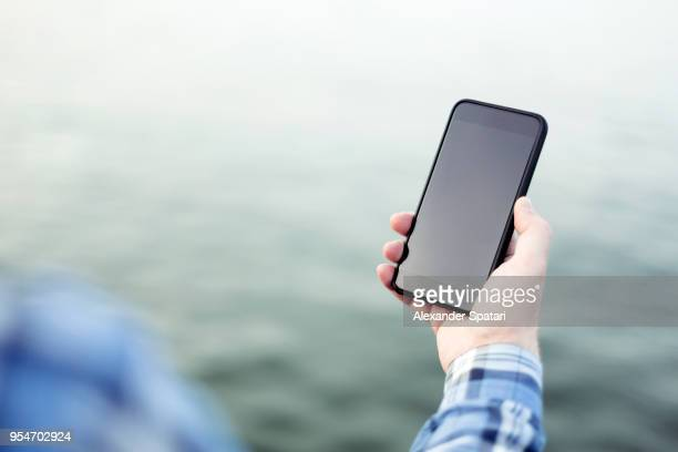 Man's hand holding a smartphone against abstract blurred water background