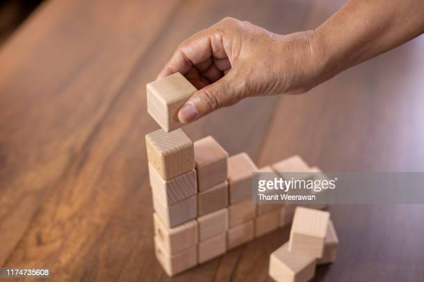 man's hand holding a top of wooden blocks over a wooden block, business and management concept. - steps - fotografias e filmes do acervo