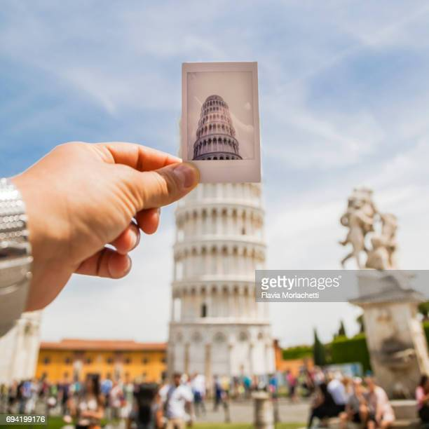 man's hand holding an instant photo against the leaning tower of pisa - leaning tower of pisa stock pictures, royalty-free photos & images