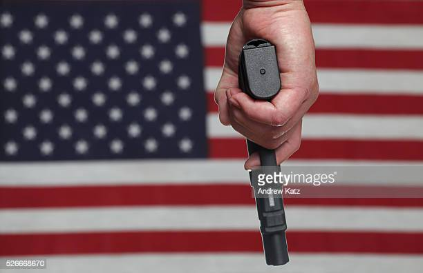 Man's hand holding autoloading handgun pointing down with slightly out of focus US flag in the background