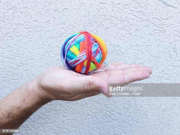 Man's hand holding ball of wool