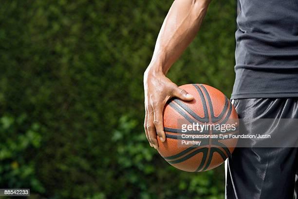 man's hand holding basketball against his leg