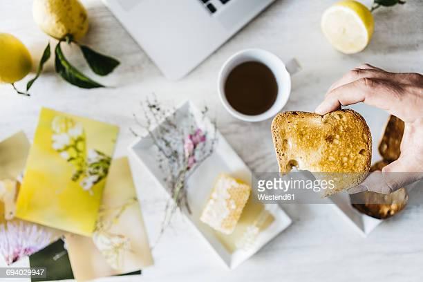 Mans hand holding bitten toast, close-up