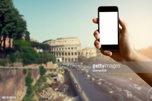 Man's Hand Holding Blank screen Mobile-phone with Blurred colosseum background