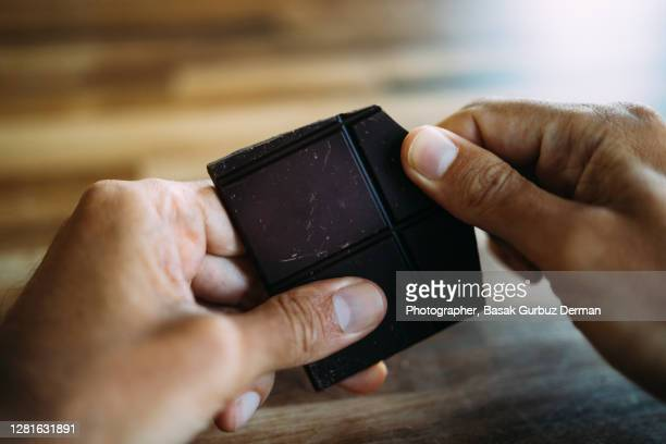 a man's hand holding / breaking a piece of chocolate - dark chocolate stock pictures, royalty-free photos & images
