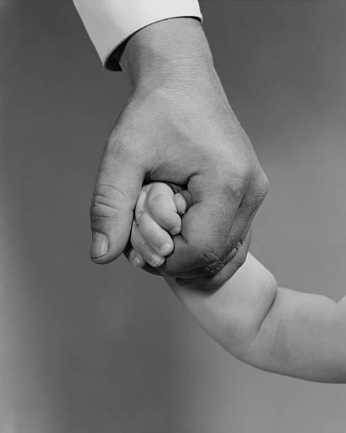 Man's hand holding child's hand.