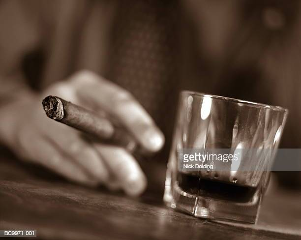 Man's hand holding cigar, resting beside glass of alcohol (toned B&W)