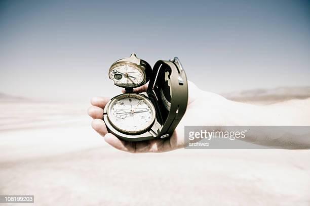 Mann Hand Holding Compass in der Mitte der Wüste