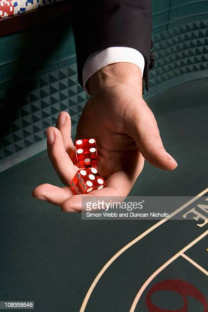 Mans hand holding dice at craps table