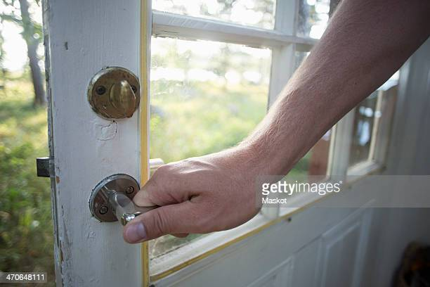 man's hand holding door handle - closing stock photos and pictures