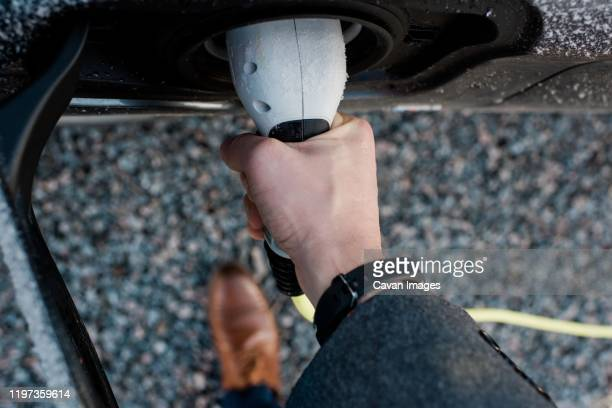 mans hand holding electric car plug - alternative fuel vehicle stock pictures, royalty-free photos & images