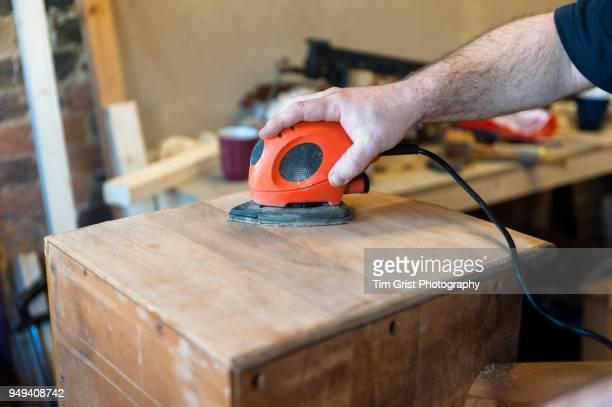 Man's Hand Holding Electric Wood Sander