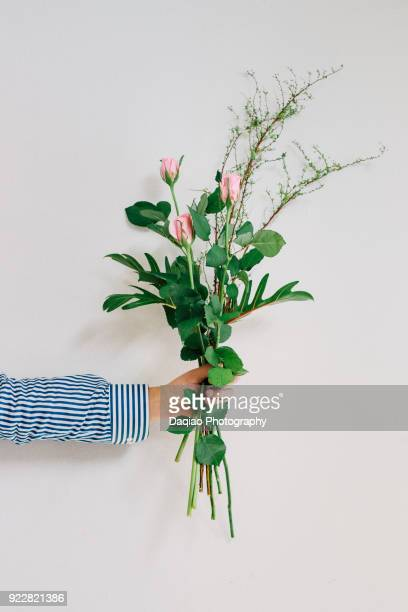 man's hand holding flowers