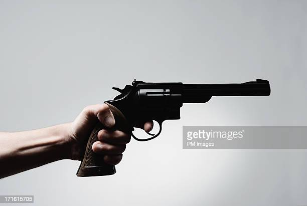 man's hand holding pistol - guns stock photos and pictures