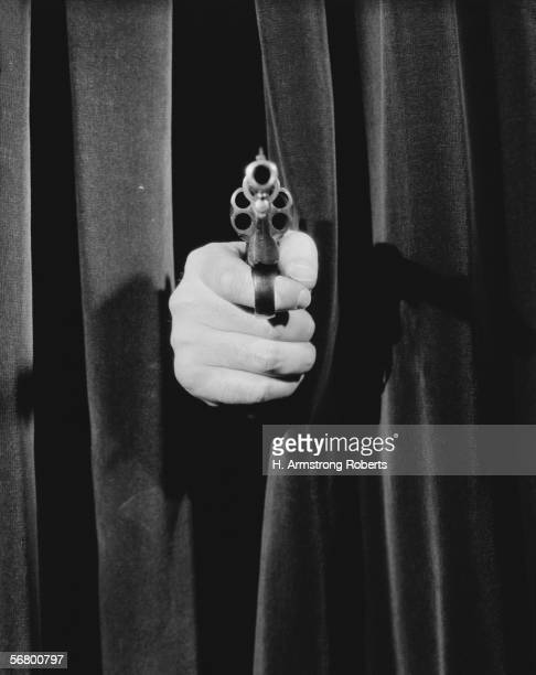 Man's hand holding pistol pointing out from behind curtain