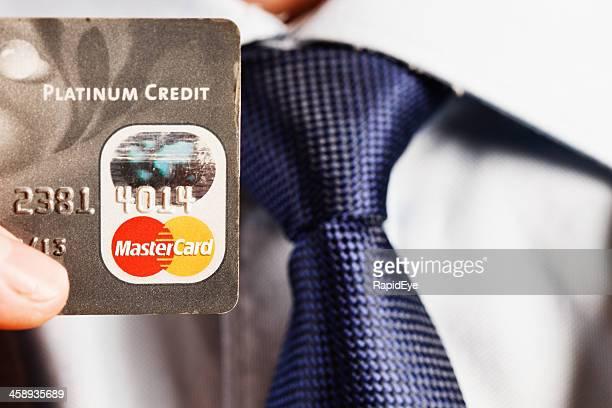 Man's hand holding Platinum Mastercard