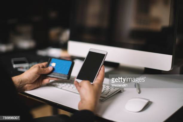 Mans hand holding smartphone and credit card at desk, partial view