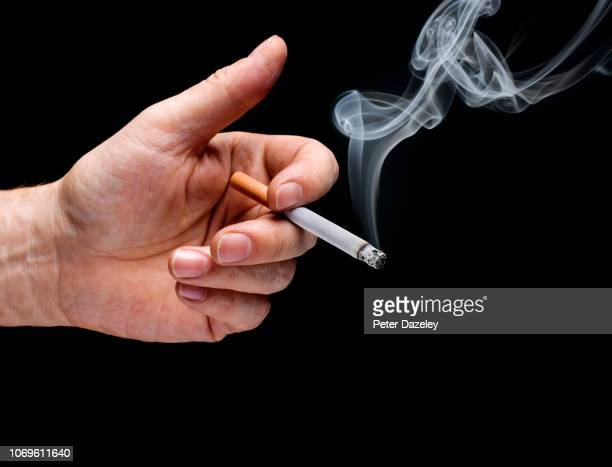 man's hand holding smoking cigarette - cigarette stock pictures, royalty-free photos & images