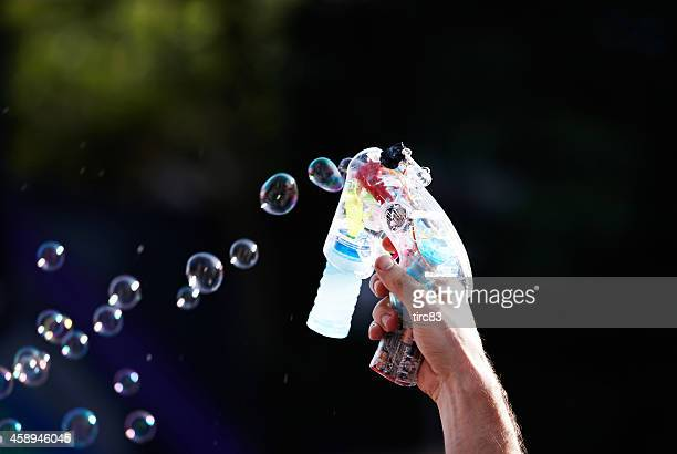 man's hand holding soap bubble gun in the air - duracell stock pictures, royalty-free photos & images