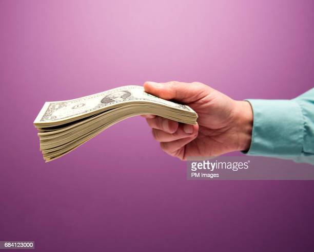 Man's hand holding stack of cash