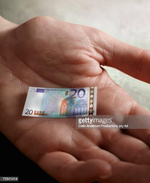 Man's hand holding tiny Euro