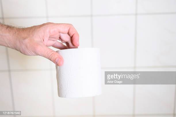 man's hand holding toilet paper in bathroom. - hemorroida imagens e fotografias de stock