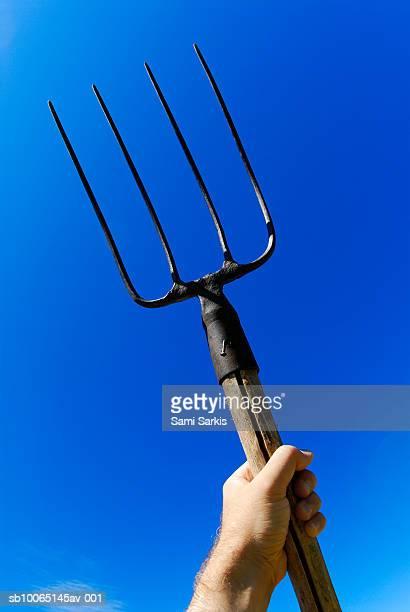 Man's hand holding up pitchfork against blue sky