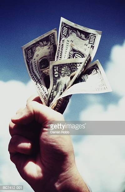 Man's hand holding various US dollar banknotes, close-up