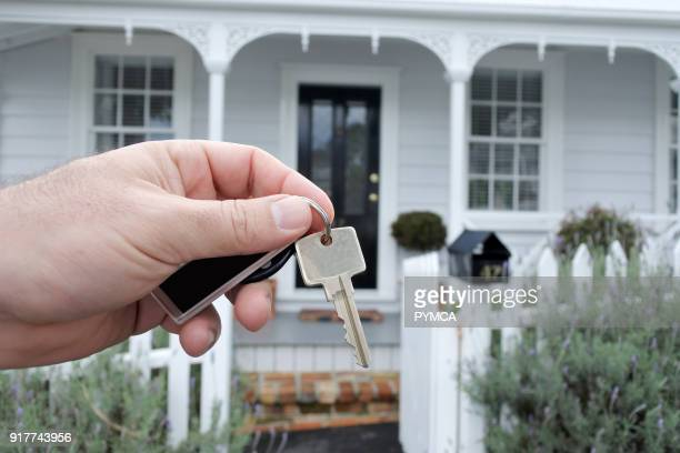 A mans hand holds a key against a front of a traditional villa house in Auckland New Zealand Buy sale real estate insurance mortgage bank loans and...