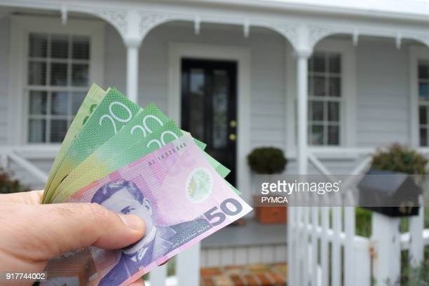 A mans hand holds NZ dollar bills against a front of a traditional villa house in Auckland New Zealand Buy sale real estate insurance mortgage bank...