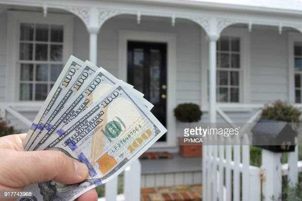 A mans hand holds US dollar bills against a front of North American house Buy sale real estate insurance mortgage bank loans and housing market...