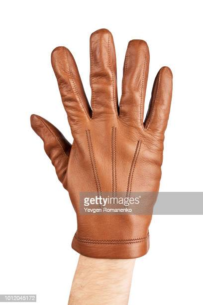 mans hand in brown leather glove - leather glove stock pictures, royalty-free photos & images