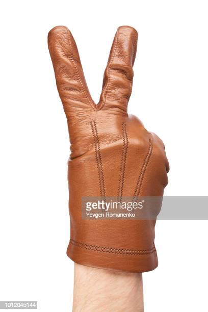 man's hand in gloves showing a victory sign - leather glove stock pictures, royalty-free photos & images