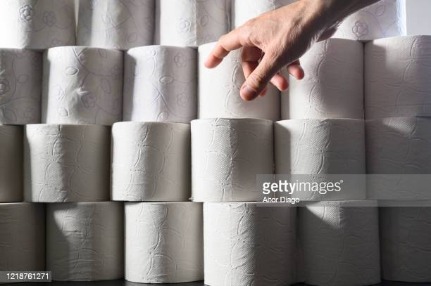 man's hand is going to take a roll of toilet paper on a table. there are  a large number of rolls of paper. storage concept. - hemorroida imagens e fotografias de stock