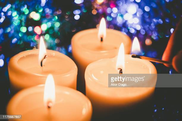 man's hand lighting a candle with a match. retro tone in advent time. christmas. - candle of hope stock pictures, royalty-free photos & images