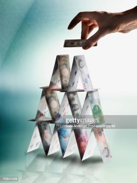 Man's hand making pyramid with world currencies