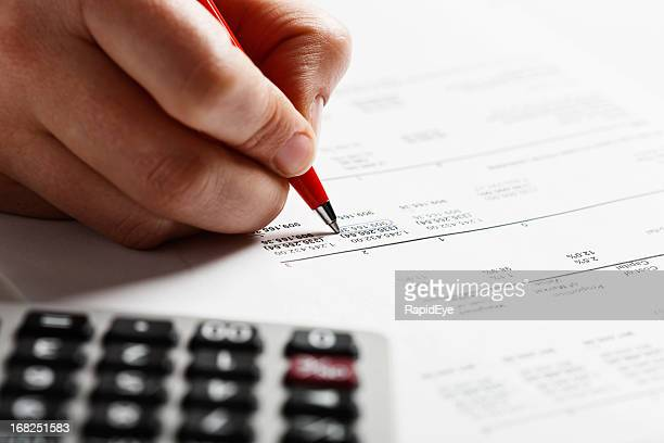 Man's hand marking items on financial document with calculator nearby