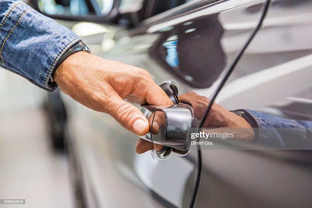 Man's hand on grey car door handle : Stock Photo