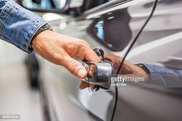 Man's hand on grey car door handle